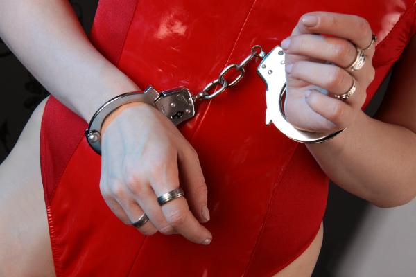 Frau in rotem Lackkleid mit Handschellen gefesselt